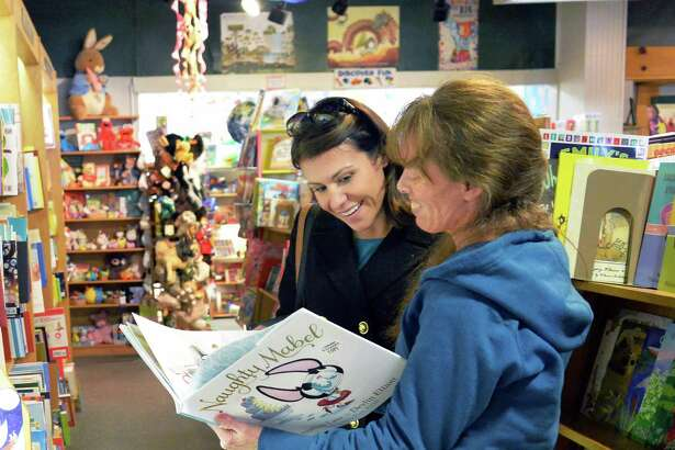 Pam Barnhart, left, of Malta, gets some help hop from children's book buyer Kathleen Kemp in The Open Door book store at Jay Street Market Place Tuesday Oct. 27, 2015 in Schenectady, NY. (John Carl D'Annibale / Times Union)