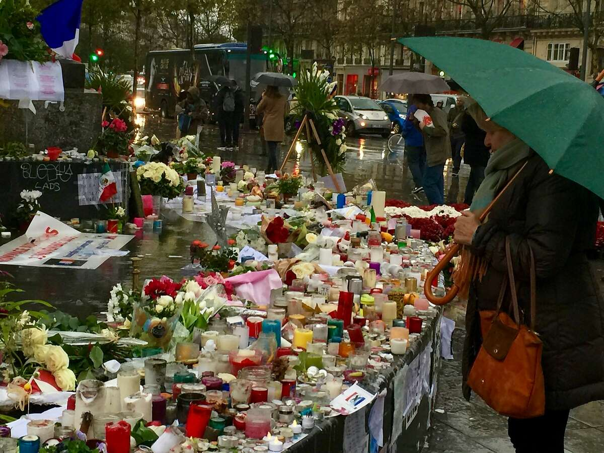 Even on a rainy day, locals and tourists go to Place de la Republique to pay respects to those killed in the ISIS attack.