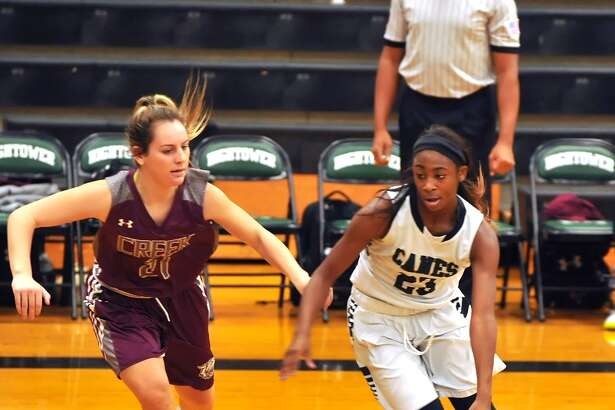 Fort Bend Hightower and Clear Creek girls basketball teams met at Hightower High School for a game as part of the Fort Bend Varsity Girls Basketball Tournament, 2015. Right, Treazure Mouton (23) of Hightower, drives toward the basket as Clear Creek's Sydney McPeters (21) defends.