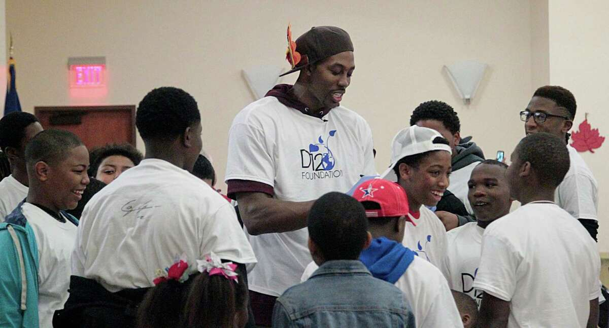 Houston Rockets center Dwight Howard signs autographs as he hosts an early Thanksgiving brunch for children enrolled in the Fifth Ward Enrichment Program Sunday, Nov. 22, 2015, in Houston.