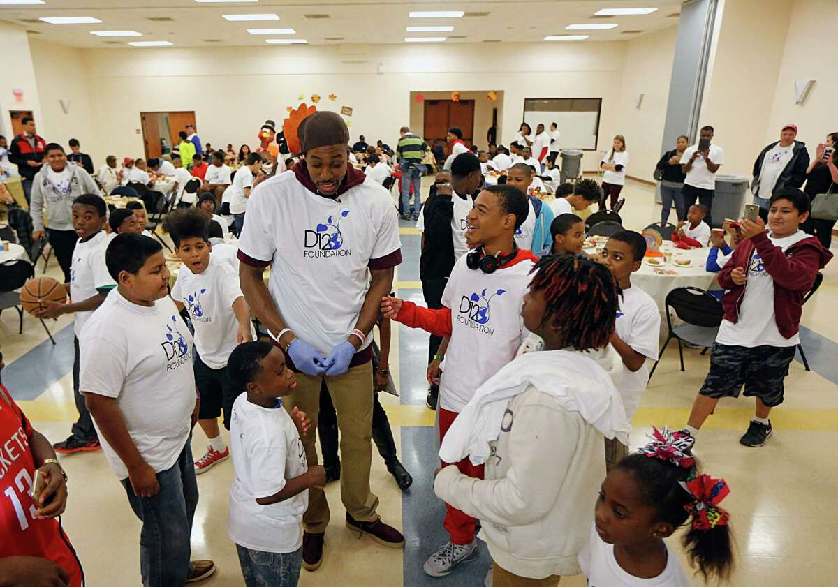 Houston Rockets center Dwight Howard chats with a group of kids as Howard hosts an early Thanksgiving brunch for children enrolled in the Fifth Ward Enrichment Program Sunday, Nov. 22, 2015, in Houston.