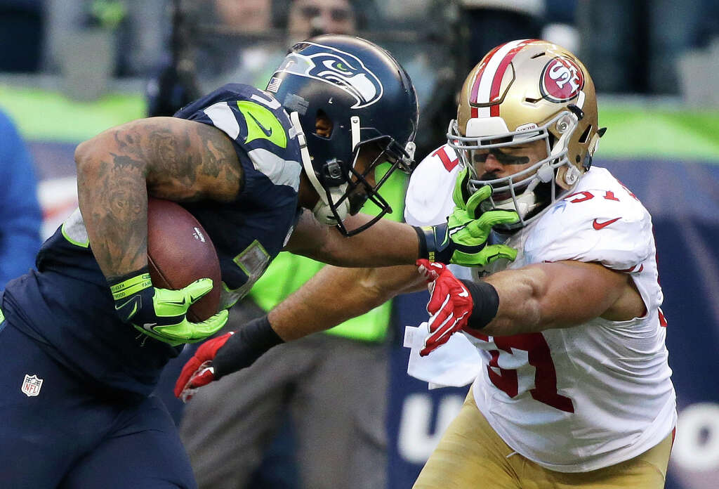 Seattle Seahawks running back Thomas Rawls, left, pushes off San Francisco 49ers inside linebacker Michael Wilhoite, right, as he runs for a touchdown during the second half of an NFL football game, Sunday, Nov. 22, 2015, in Seattle. (AP Photo/Elaine Thompson) Photo: Elaine Thompson, Associated Press / AP