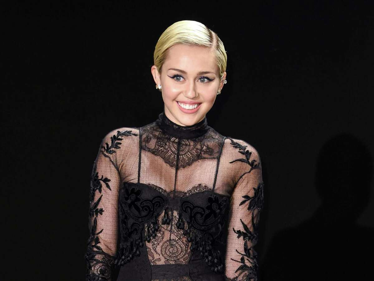 """FILE - In this Feb. 20, 2015 file photo, Miley Cyrus arrives at the Tom Ford Autumn/Winter 2015 Womenswear Presentation in Los Angeles. On Oct. 3, Cyrus will return as host for a third time to kick off the 41st season of """"Saturday Night Live."""" (Photo by Rob Latour/Invision/AP, File) ORG XMIT: NYET101"""