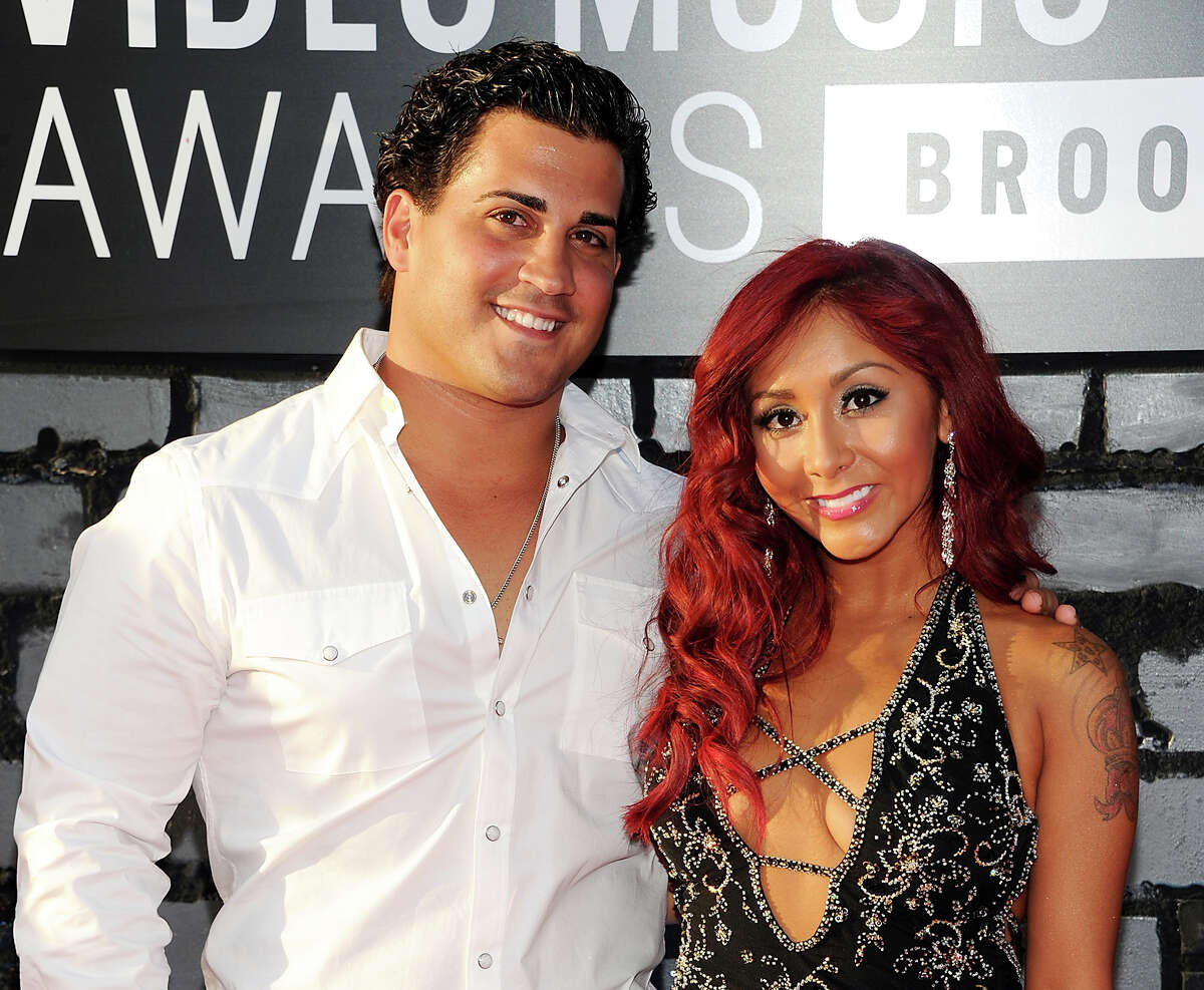 """FILE - In this Aug. 25, 2013 file photo, Nicole """"Snooki"""" Polizzi, right, and Jionni LaValle arrive at the MTV Video Music Awards in the Brooklyn borough of New York. Snooki has officially tied the knot. Former ?""""Jersey Shore?"""" star Polizzi married boyfriend LaValle in a church ceremony Saturday, Nov. 29, 2014, in East Hanover, about 15 miles west of New York City. (Photo by Evan Agostini/Invision/AP, File) ORG XMIT: NY119"""