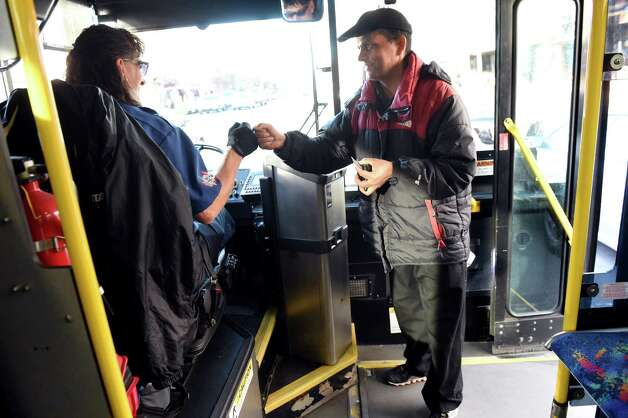 Ajaya Adhikari of Saratoga Springs, right, boards the CDTA bus and fist bumps driver Pat Caccavo on Wednesday, Nov. 18, 2015, in Saratoga Springs, N.Y. Adhikari was headed to his job at Skidmore College. (Cindy Schultz / Times Union) Photo: Cindy Schultz / 10034341A