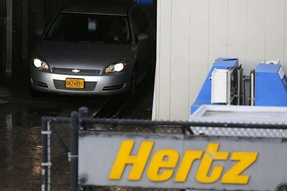 A Hertz rental car goes through a car wash at San Francisco International Airport in San Francisco, California, on Sunday, Nov. 22, 2015.