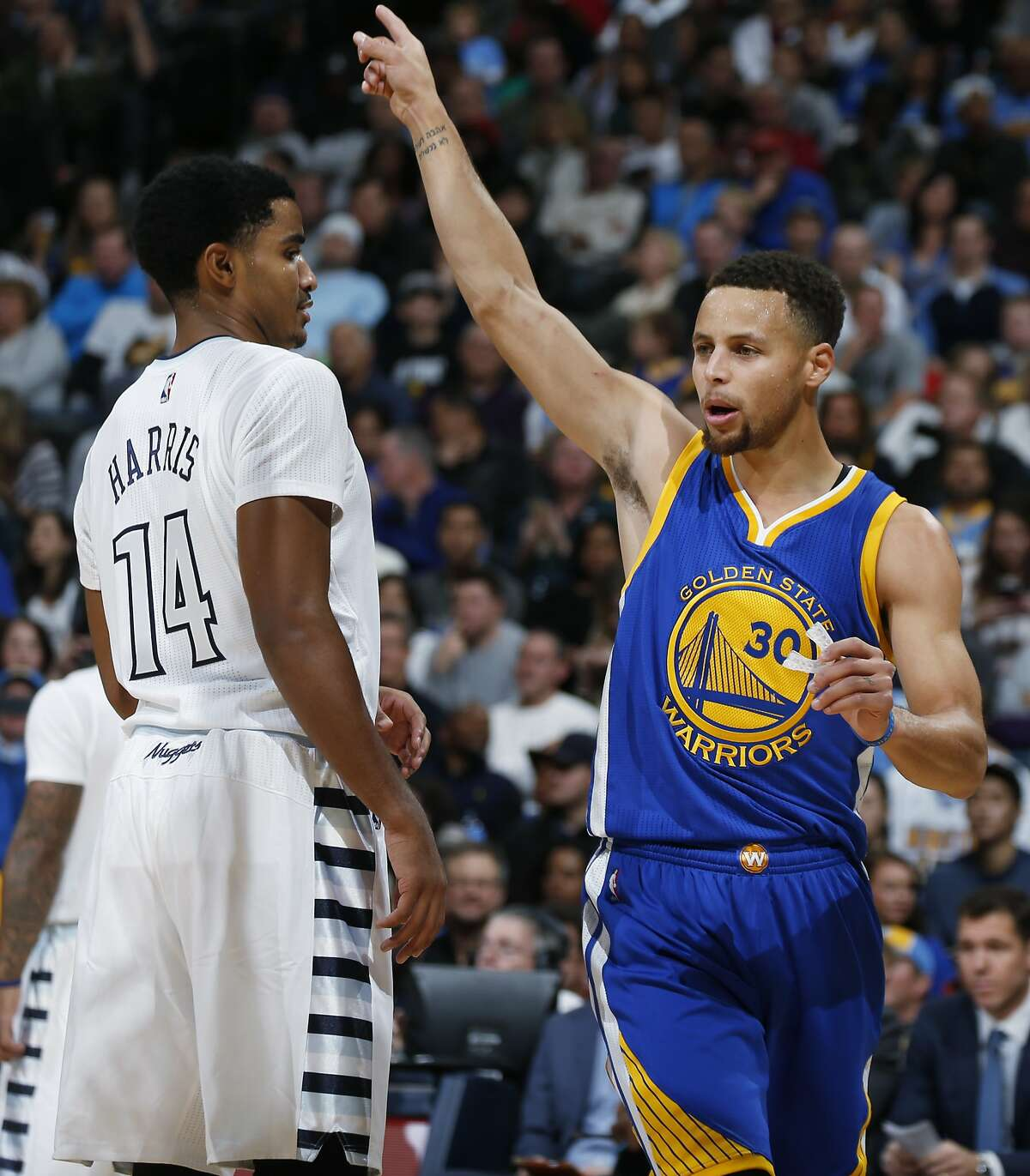Golden State Warriors guard Stephen Curry, right, gestures after a Warriors basket as Denver Nuggets guard Gary Harris looks on in the first half of an NBA basketball game Sunday, Nov. 22, 2015, in Denver.