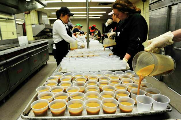 Volunteers pour gravy into single serve cups at the Empire State Plaza on Sunday, Nov. 22, 2015, in Albany, N.Y.  as over 500 volunteers help Sunday to prepare for the Equinox 46th Annual Thanksgiving Day Community Dinner that will be served on Thanksgiving.  A total of 3,500 volunteers help to put on the yearly event which feeds roughly 10,000 people.  On Thanksgiving Day some 9,500 meals will be delivered in a 40 mile radius from Albany and 500 meals will be served as a sit-down for those coming in.  As in years past Equinox is in need of drivers to deliver the meals Thanksgiving morning.  Anyone interested in volunteering can call the Equinox hotline at 518-434-0131.  Price Chopper/Market 32 donated 12,000 pounds of turkey, Hannaford Supermarkets donated 1,200 pies and local farms, businesses, church groups and school group and individuals all donated food items for the event.(Paul Buckowski / Times Union)