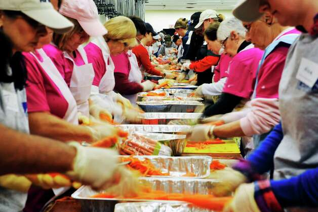 Volunteers peel carrots at the Empire State Plaza on Sunday, Nov. 22, 2015, in Albany, N.Y.  as over 500 volunteers help Sunday to prepare for the Equinox 46th Annual Thanksgiving Day Community Dinner that will be served on Thanksgiving.  A total of 3,500 volunteers help to put on the yearly event which feeds roughly 10,000 people.  On Thanksgiving Day some 9,500 meals will be delivered in a 40 mile radius from Albany and 500 meals will be served as a sit-down for those coming in.  As in years past Equinox is in need of drivers to deliver the meals Thanksgiving morning.  Anyone interested in volunteering can call the Equinox hotline at 518-434-0131.  Price Chopper/Market 32 donated 12,000 pounds of turkey, Hannaford Supermarkets donated 1,200 pies and local farms, businesses, church groups and school group and individuals all donated food items for the event.(Paul Buckowski / Times Union)