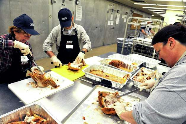 Volunteers Barb Pelersi, left, of Glenmont, her husband Don Pelersi, center, and Kimmarie Victoria of Colonie, carve white meat from cooked turkeys at the Empire State Plaza on Sunday, Nov. 22, 2015, in Albany, N.Y.  as over 500 volunteers help Sunday to prepare for the Equinox 46th Annual Thanksgiving Day Community Dinner that will be served on Thanksgiving.  A total of 3,500 volunteers help to put on the yearly event which feeds roughly 10,000 people.  On Thanksgiving Day some 9,500 meals will be delivered in a 40 mile radius from Albany and 500 meals will be served as a sit-down for those coming in.  As in years past Equinox is in need of drivers to deliver the meals Thanksgiving morning.  Anyone interested in volunteering can call the Equinox hotline at 518-434-0131.  Price Chopper/Market 32 donated 12,000 pounds of turkey, Hannaford Supermarkets donated 1,200 pies and local farms, businesses, church groups and school group and individuals all donated food items for the event.(Paul Buckowski / Times Union)