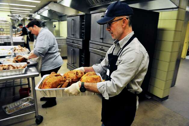 Volunteer Don Pelersi of Glenmont carries a tray of cooked turkeys over to a table to carve them up at the Empire State Plaza on Sunday, Nov. 22, 2015, in Albany, N.Y. as over 500 volunteers help Sunday to prepare for the Equinox 46th Annual Thanksgiving Day Community Dinner that will be served on Thanksgiving.  A total of 3,500 volunteers help to put on the yearly event which feeds roughly 10,000 people.  On Thanksgiving Day some 9,500 meals will be delivered in a 40 mile radius from Albany and 500 meals will be served as a sit-down for those coming in.  As in years past Equinox is in need of drivers to deliver the meals Thanksgiving morning.  Anyone interested in volunteering can call the Equinox hotline at 518-434-0131.  Price Chopper/Market 32 donated 12,000 pounds of turkey, Hannaford Supermarkets donated 1,200 pies and local farms, businesses, church groups and school group and individuals all donated food items for the event.(Paul Buckowski / Times Union)