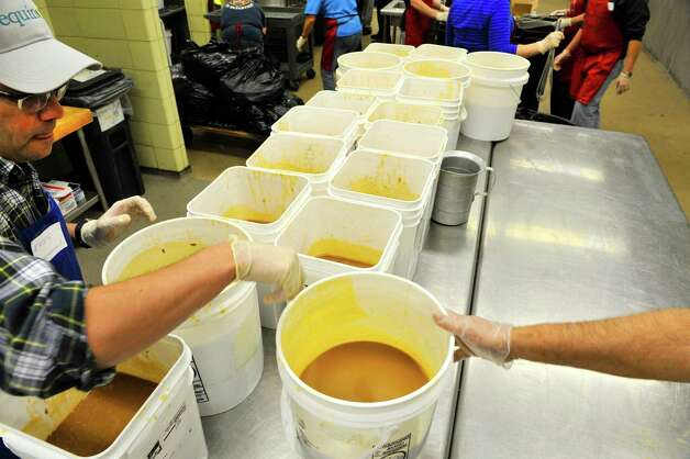 Volunteer Ennio Corsi of Albany lines up buckets of gravy that have cooled at the Empire State Plaza on Sunday, Nov. 22, 2015, in Albany, N.Y.  as over 500 volunteers help Sunday to prepare for the Equinox 46th Annual Thanksgiving Day Community Dinner that will be served on Thanksgiving.  Corsi was there with a group from All Saints Catholic Church.  A total of 3,500 volunteers help to put on the yearly event which feeds roughly 10,000 people.  On Thanksgiving Day some 9,500 meals will be delivered in a 40 mile radius from Albany and 500 meals will be served as a sit-down for those coming in.  As in years past Equinox is in need of drivers to deliver the meals Thanksgiving morning.  Anyone interested in volunteering can call the Equinox hotline at 518-434-0131.  Price Chopper/Market 32 donated 12,000 pounds of turkey, Hannaford Supermarkets donated 1,200 pies and local farms, businesses, church groups and school group and individuals all donated food items for the event.(Paul Buckowski / Times Union)