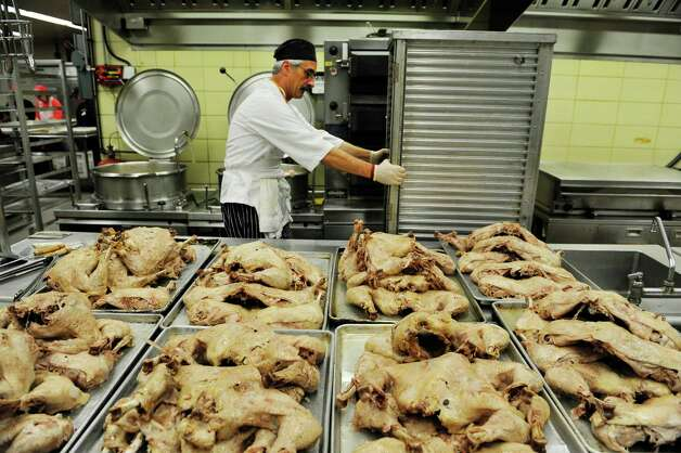 Volunteer chef Paul Strasser wheels a cart of turkeys past trays of cooked turkeys cooling off at the Empire State Plaza on Sunday, Nov. 22, 2015, in Albany, N.Y.  as over 500 volunteers help Sunday to prepare for the Equinox 46th Annual Thanksgiving Day Community Dinner that will be served on Thanksgiving.  A total of 3,500 volunteers help to put on the yearly event which feeds roughly 10,000 people.  On Thanksgiving Day some 9,500 meals will be delivered in a 40 mile radius from Albany and 500 meals will be served as a sit-down for those coming in.  As in years past Equinox is in need of drivers to deliver the meals Thanksgiving morning.  Anyone interested in volunteering can call the Equinox hotline at 518-434-0131.  Price Chopper/Market 32 donated 12,000 pounds of turkey, Hannaford Supermarkets donated 1,200 pies and local farms, businesses, church groups and school group and individuals all donated food items for the event.(Paul Buckowski / Times Union)