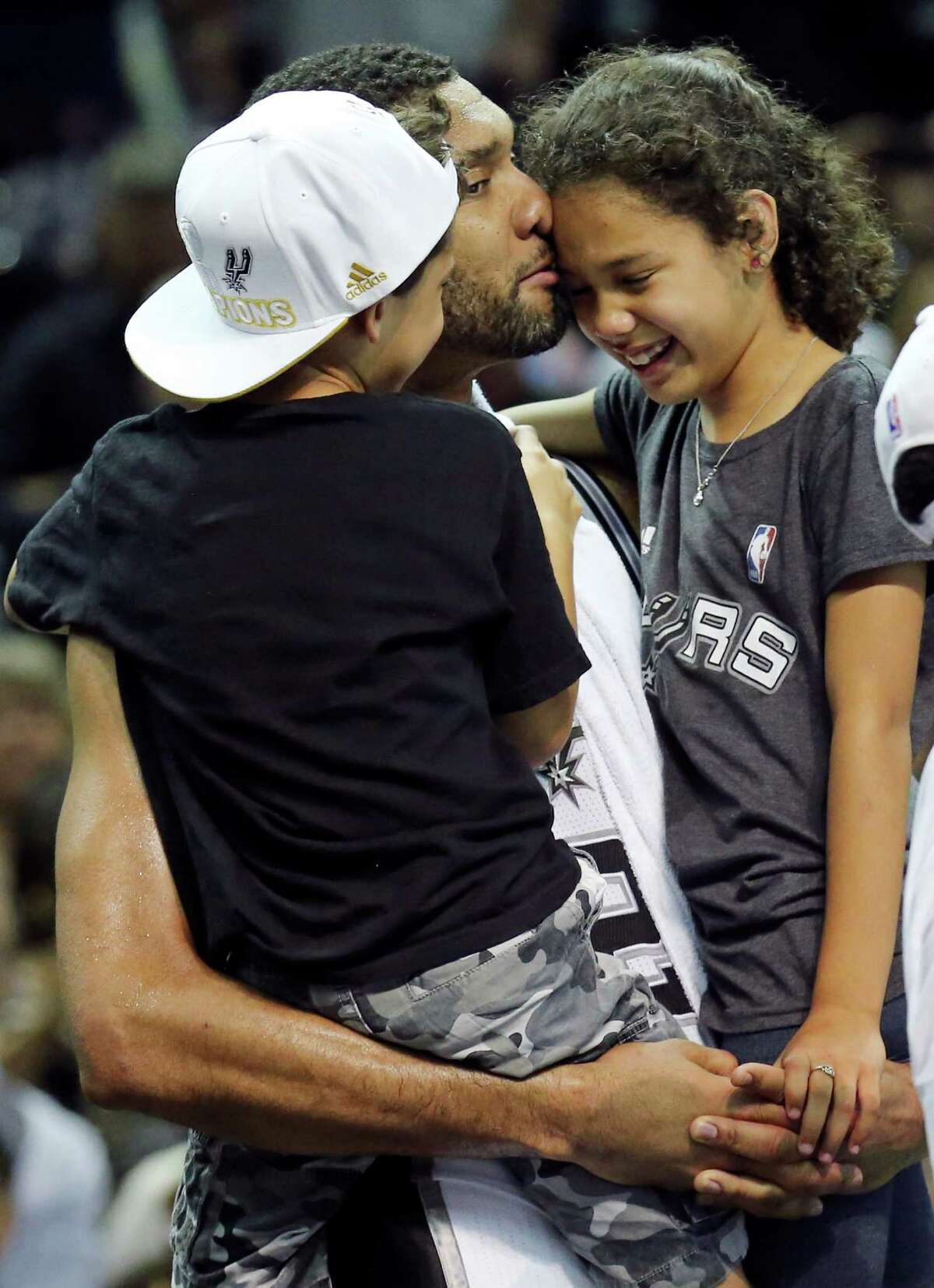 San Antonio Spurs' Tim Duncan holds his children Draven (left) and Sydney after Game 5 of the 2014 NBA Finals against the Miami Heat on June 15, 2014 at the AT&T Center. The Spurs won 104-87.