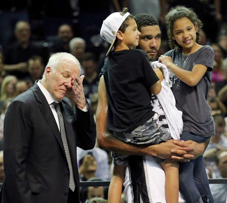 San Antonio Spurs' Tim Duncan holds his children Draven (left) and Sydney as head coach Gregg Popovich wipes away tears after Game 5 of the 2014 NBA Finals against the Miami Heat on June 15, 2014 at the AT&T Center. The Spurs won 104-87. Photo: Edward A. Ornelas /San Antonio Express-News / © 2014 San Antonio Express-News
