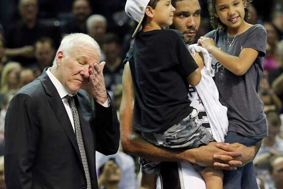 San Antonio Spurs' Tim Duncan holds his children Draven (left) and Sydney as head coach Gregg Popovich wipes away tears after Game 5 of the 2014 NBA Finals against the Miami Heat on June 15, 2014 at the AT&T Center. The Spurs won 104-87.