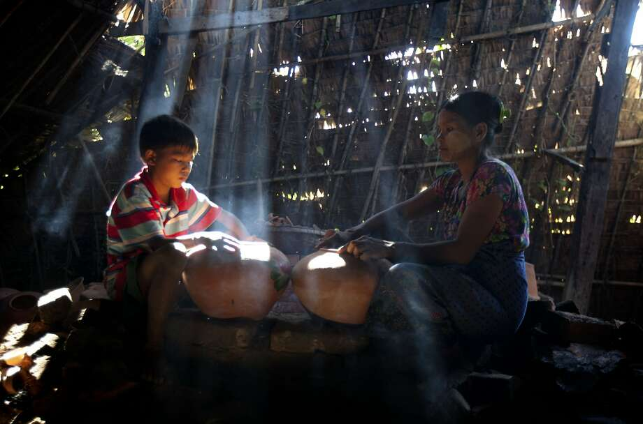 A boy helps his mother to make earthen pots at their home factory Sunday, Nov. 22, 2015, in Twantay township on the outskirts of Yangon, Myanmar. Photo: Khin Maung Win, Associated Press