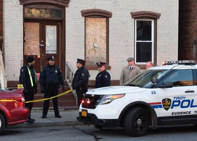 Troy police comb the scene of an early morning stabbing that left a woman in Troy dead and police searching for a 45-year-old man. (Skip Dickstein / Times Union)