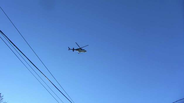 A State Police helicopter hovers over Troy as police search for the man they suspected stabbed a woman to death on Sixth Avenue early Monday morning. Police said the search was focused on Oakwood Cemetery.  (Skip Dickstein / Times Union)