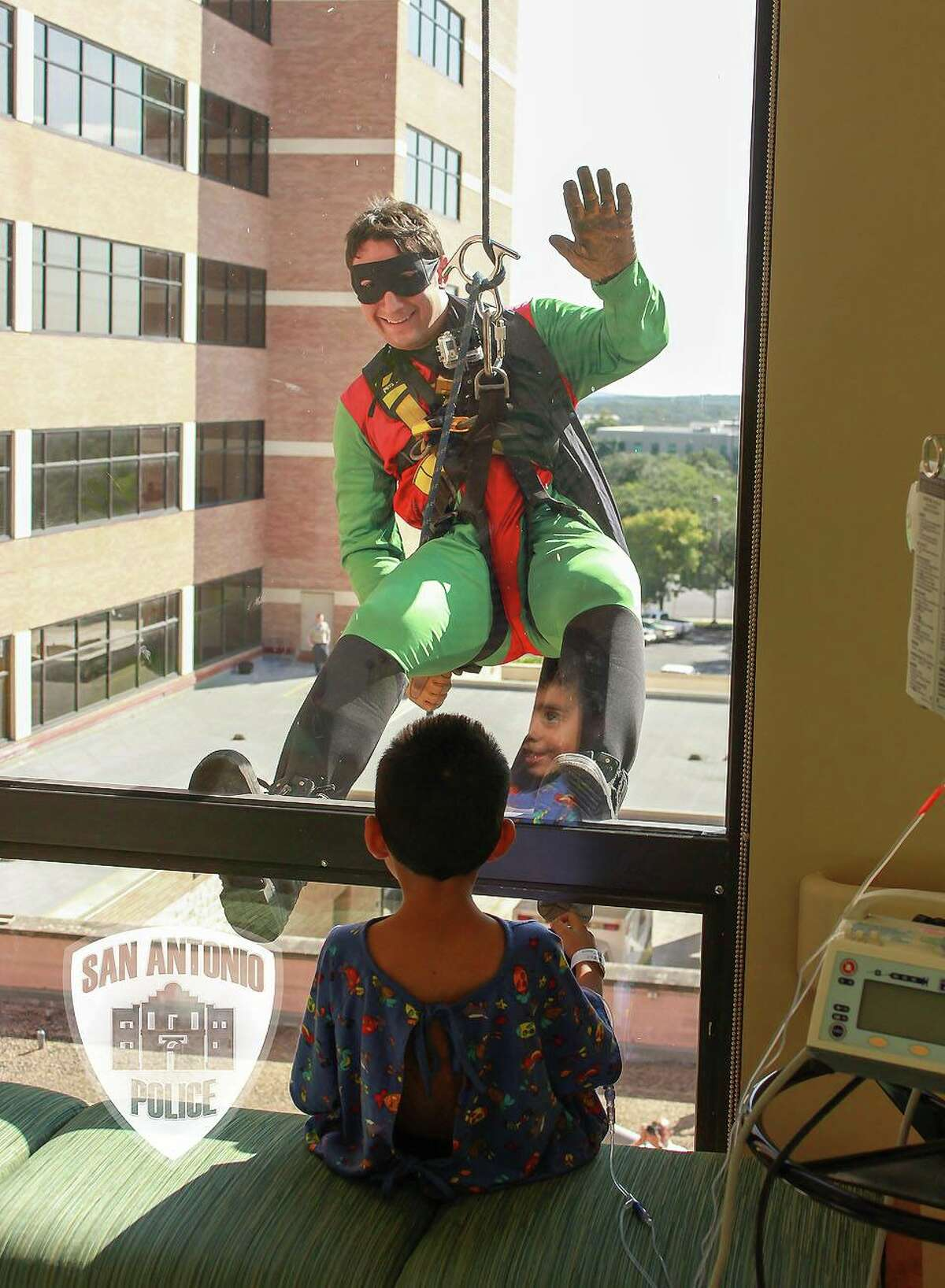 San Antonio police and firefighters visited pediatric patients at North Central Baptist Hospital Friday as popular superheros.