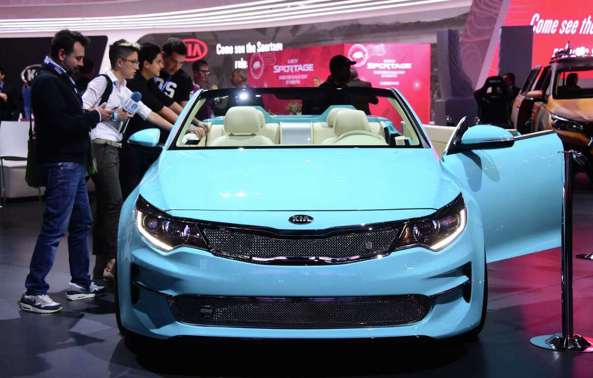 Journalists look at the 2016 Kia Optima Convertible Concept car at the 2015 Los Angeles Auto Show in Los Angeles, California on November 18, 2015. The LA Auto Show opens to the public on November 20.