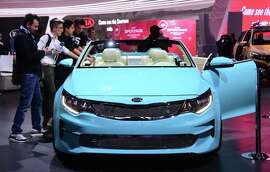 Journalists look at the 2016 Kia Optima Convertible Concept car at the 2015 Los Angeles Auto Show in Los Angeles, California on November 18, 2015. The LA Auto Show opens to the public on November 20. AFP PHOTO/ FREDERIC J. BROWN