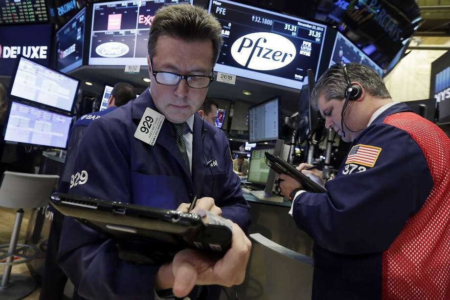 Traders James Matthews (left) and John Panin work at the post that handles Pfizer on the floor of the New York Stock Exchange. Photo: Richard Drew, Associated Press