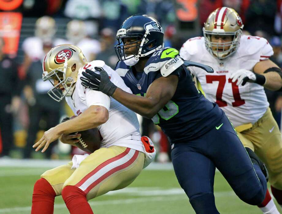 Seattle Seahawks defensive end Cliff Avril, center, sacks San Francisco 49ers quarterback Blaine Gabbert, left, in the second half of an NFL football game, Sunday, Nov. 22, 2015, in Seattle.  Photo: Elaine Thompson, Associated Press / AP