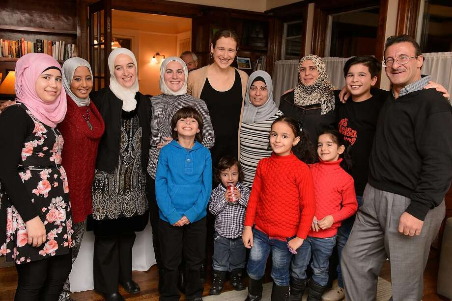 EVANSTON, IL - NOVEMBER 20:  Executive Director of MoveOn.org Civic Action Anna Galland, Representative Jan Schakowsky, Evanston Mayor Elizabeth Tisdahl and families pose together as Syrian refugees and community leaders join for a #RefugeesWelcome Thanksgiving dinner hosted by MoveOn.org on November 20, 2015 in Evanston, Illinois.  (Photo by Daniel Boczarski/Getty Images for MoveOn.org) Photo: Daniel Boczarski, Getty Images For MoveOn.org