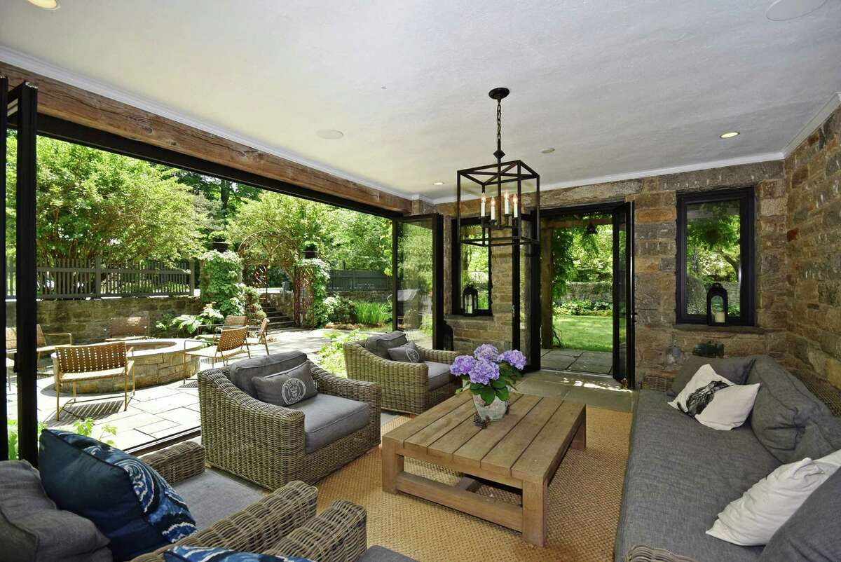 Four walls of glass windows and doors in the pool house open for al fresco entertaining alongside a built-in fire pit.