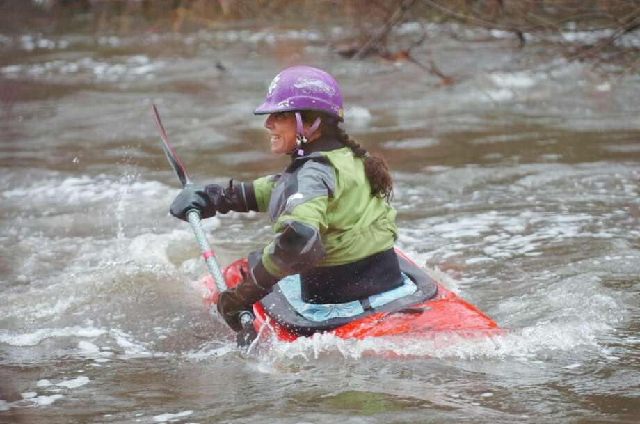Jessie Stone, from Purchase, NY, kayaks on the Byram River on Tuesday, March 30, 2010.  Stone is a member of the women's free style kayak team.  She is also a white water kayaker, and was glad to have some white water to work out on. Photo: Helen Neafsey / Greenwich Time