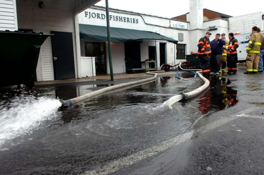 Cos Cob Fire Police pump out the cellar of the Greenwich Laundry. The sewer backed up causing the flood, on Tuesday, March 30, 2010.