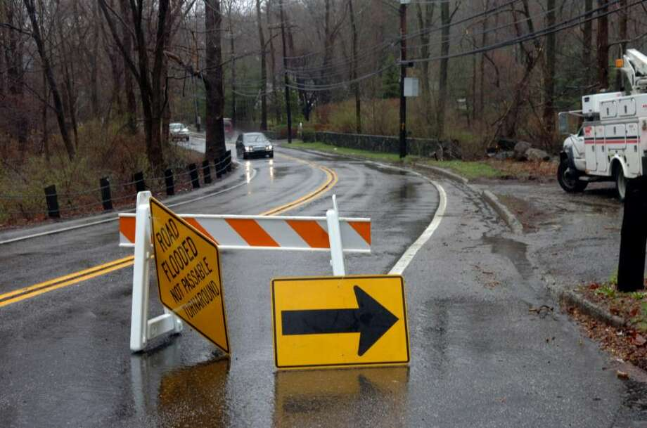 The Riversville Road was flooded in the rain storm on Tuesday, March 30, 2010. Photo: Helen Neafsey / Greenwich Time