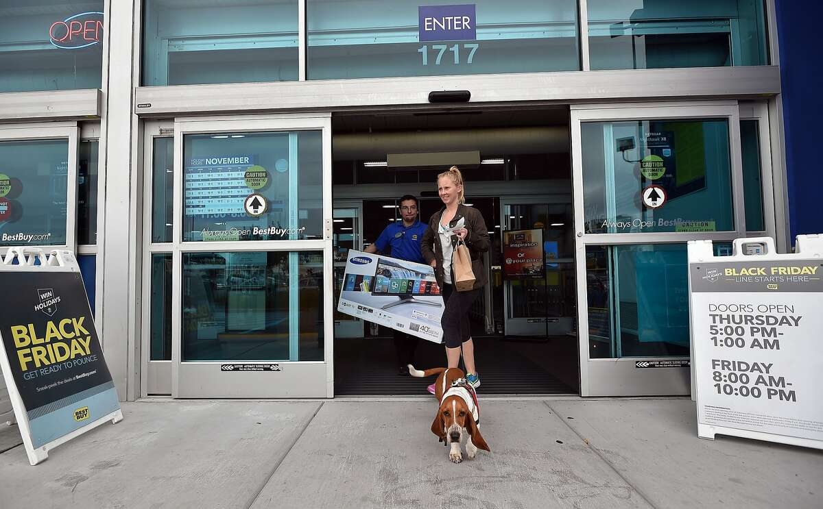 Liz Wendorf exits a Best Buy store after picking up a sale item in San Francisco on November 23, 2015. Retailers are facing a tough holiday shopping season as weak wage growth continues to restrain consumer spending.