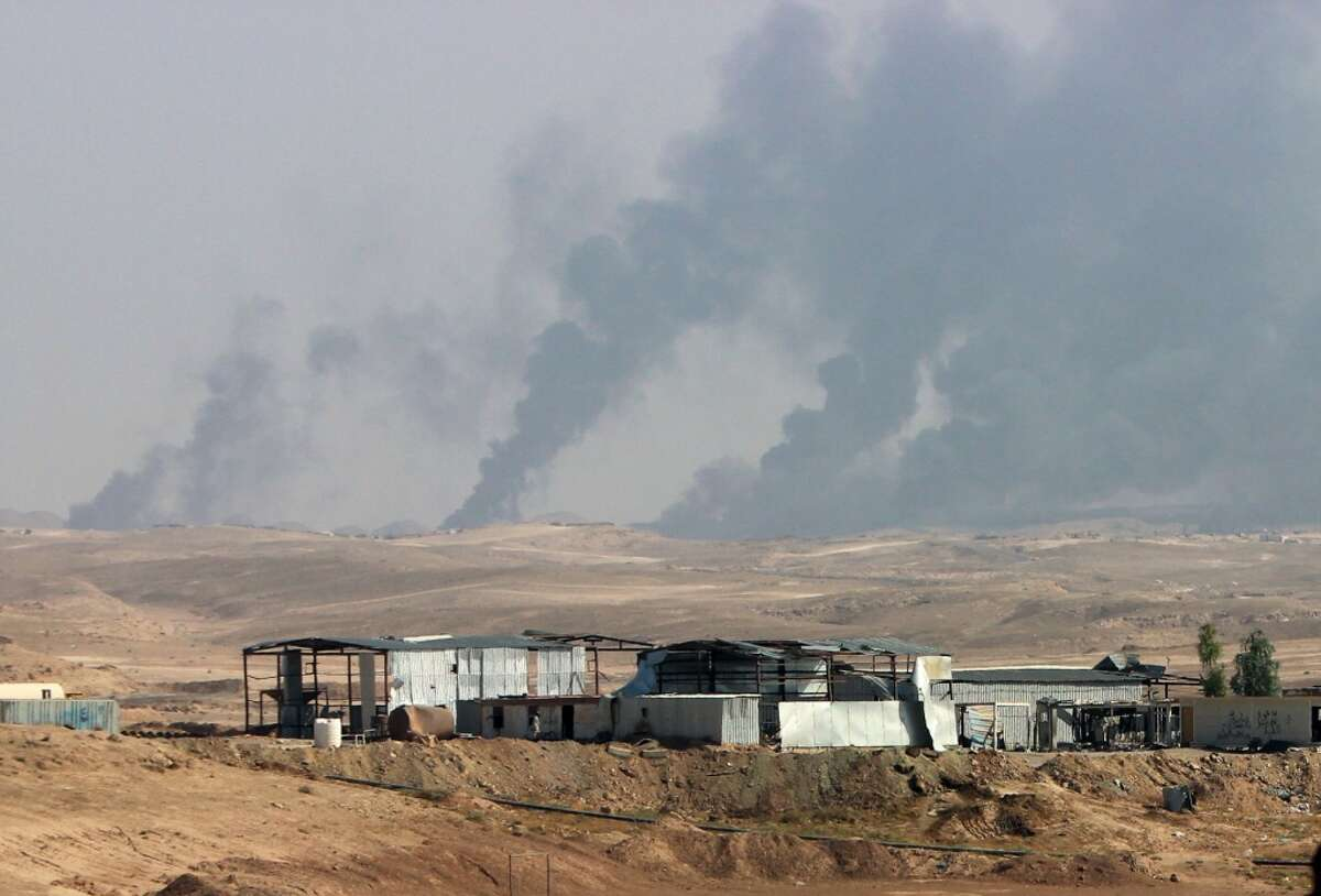 FILE - In this Saturday, Oct. 24, 2015, file photo, smoke rises as Iraqi security forces and allied Popular Mobilization Forces shell Islamic State group positions at an oil field outside Beiji, some 250 kilometers (155 miles) north of Baghdad, Iraq. The United States and Russia are going after the Islamic State group?'s oil industry, destroying refineries and hundreds of tanker trucks transporting oil from eastern Syria in a heavy bombardment in recent days aiming to break the extremists?' biggest source of income. (AP Photo, File)