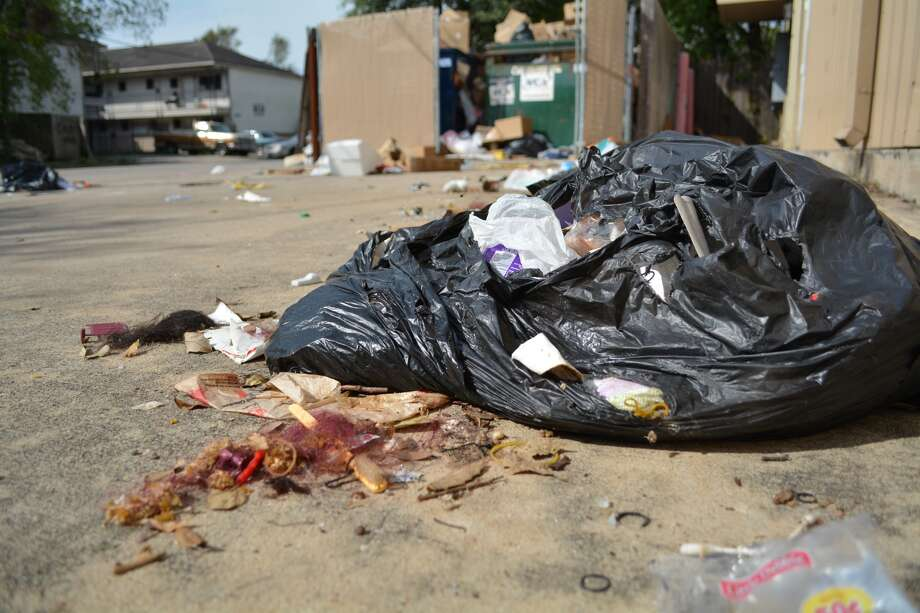 A recent photo of garbage overflowing from a Dumpster and bags dumped outside a local business in a south Houston neighborhood. Photo: John D. Harden, Houston Chronicle