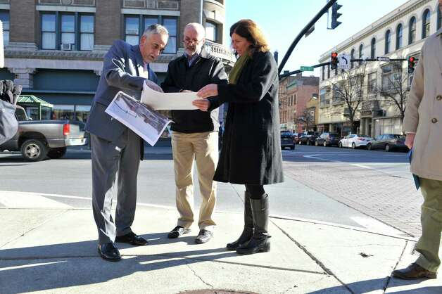 Carm Basile, left, CEO of CDTA, shows plans to Patrick Madden, center, Troy mayor elect and Carmella Mantello, city council president-elect, during a tour of the future CDTA Troy Transit Center at Fulton St. and Fourth St. on Monday, Nov. 23, 2015, in downtown Troy, N.Y. (Paul Buckowski / Times Union) Photo: PAUL BUCKOWSKI / 10034394A