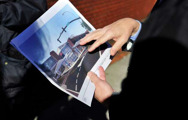 Carm Basile, CEO of CDTA, shows points to an artist's rendition of a proposed transit center during a tour of the future CDTA Troy Transit Center at Fulton St. and Fourth St. on Monday, Nov. 23, 2015, in downtown Troy, N.Y. (Paul Buckowski / Times Union) Photo: PAUL BUCKOWSKI / 10034394A