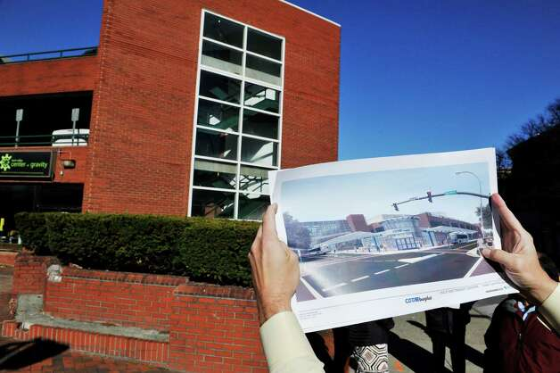 An artist's rendition of the proposed CDTA Troy Transit Center is held up at the location of  Fulton St. and Fourth St. on Monday, Nov. 23, 2015, in downtown Troy, N.Y. (Paul Buckowski / Times Union) Photo: PAUL BUCKOWSKI / 10034394A
