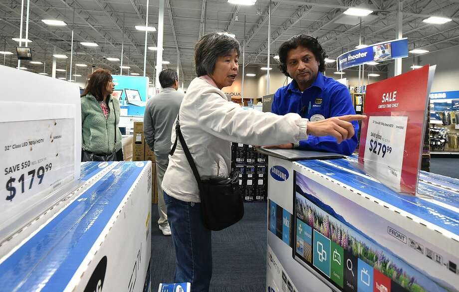 A shopper who declined to give her name is helped by Best Buy employee Shane Krishna (R) at a Best Buy store in San Francisco on November 23, 2015. Retailers face a tough holiday shopping season as weak wage growth continues to restrain consumer spending. Photo: JOSH EDELSON / SAN FRANCISCO CHR