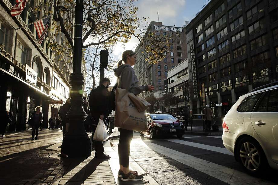 Ashley Pelletier waits to cross Market Street while shopping in San Francisco, Calif., on Monday, November 23, 2015. Holiday shoppers started their crusades in earnest on Monday, getting ready for or ahead of the masses expected on Friday, when shopping begins after Thanksgiving. Photo: Carlos Avila Gonzalez, The Chronicle