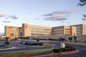 Methodist Stone Oak Hospital is expanding by more than 100,000 square feet, adding 71 inpatient beds to the hospital. The new addition, shown in the center of this rendering, features a tower marked with a cross and a flame and an adjoining L-shaped building with glass windows.