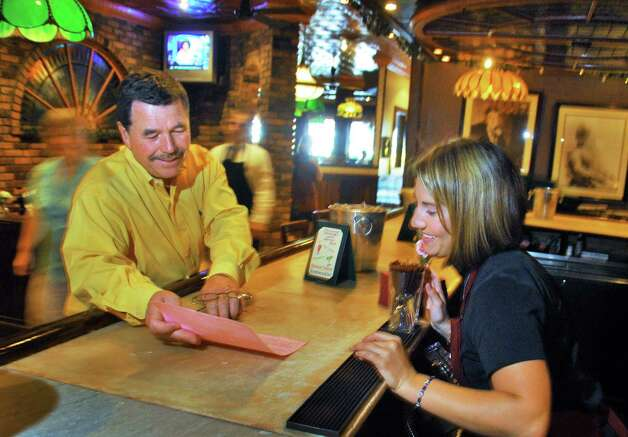 Restaurant owner Ray Morris, left, reviews specials with employee Megan Marshall, 26, of Glens Falls, at Lillian's Restaurant on Broadway in Saratoga Springs Wednesday afternoon, Aug. 27, 2008. (John Carl D'Annibale / Times Union) Photo: John Carl D'Annibale / Albany Times Union