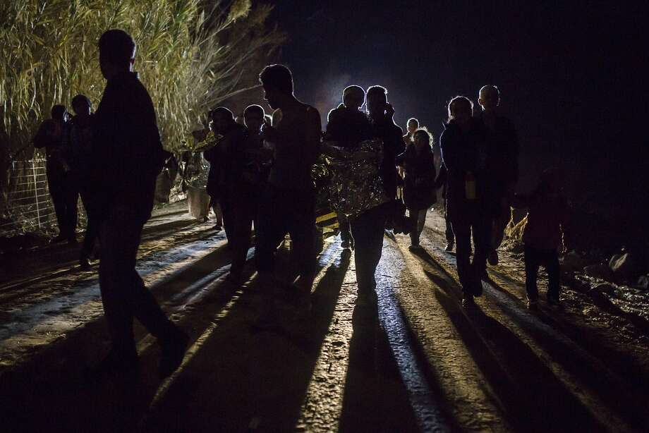 "Refugees and migrants walk across a road after arriving on a dinghy from a Turkish coast to the northeastern Greek island of Lesbos, on Monday, Nov. 23, 2015. Several European countries, including EU members Slovenia and Croatia and non-members Serbia and Macedonia, have declared they will only allow ""war-zone refugees"" from Afghanistan, Iraq and Syria to transit through their countries on their way to central and northern Europe.  Photo: Santi Palacios, Associated Press"