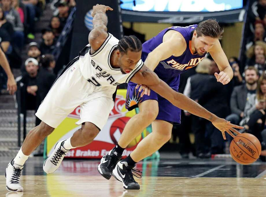 San Antonio Spurs' Kawhi Leonard and Phoenix Suns' Mirza Teletovic grab for a loose ball during first half action Monday Nov. 23, 2015 at the AT&T Center. Photo: Edward A. Ornelas, San Antonio Express-News / © 2015 San Antonio Express-News