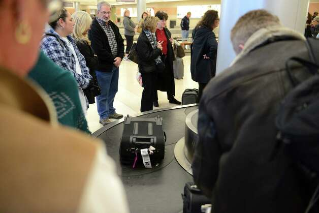Air passengers collect their bags at Albany International Airport  Monday lunchtime, Nov. 23, 2015, in Colonie, N.Y.  (Will Waldron/Times Union) Photo: Will Waldron / 10034406A