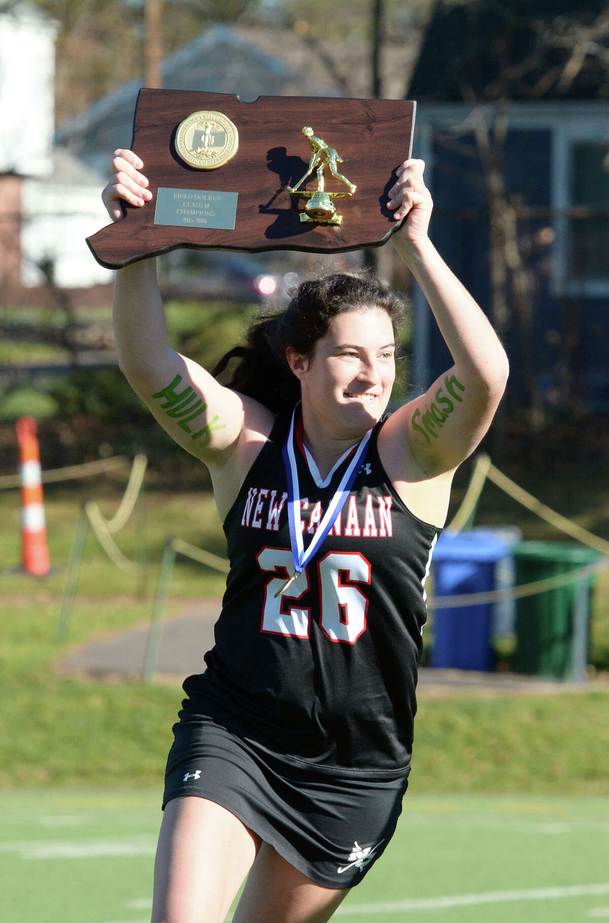 New Canaan's Sarah Jorgensen (26) hoists the first-place trophy at the conclusion of Saturday's game.