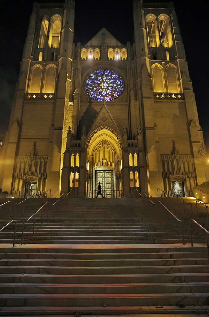 A pedestrian walks by the front of Grace Cathedral in San Francisco, Calif., on Monday, November 23, 2015. Grace Cathedral has a new look now that the stained glass rose is lighted by a daylight balanced spotlight allowing all the correct colors to be visible. In addition, two spotlights in the arcade above the rose window project colors onto the cathedral's steps. Photo: Carlos Avila Gonzalez, The Chronicle