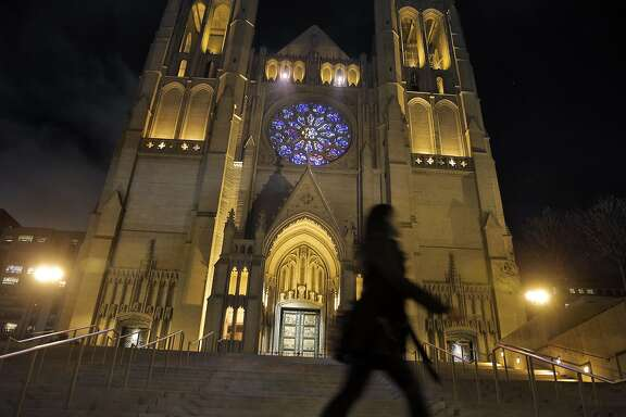 A pedestrian walks by the front of Grace Cathedral in San Francisco, Calif., on Monday, November 23, 2015. Grace Cathedral has a new look now that the stained glass rose is lighted by a daylight balanced spotlight allowing all the correct colors to be visible. In addition, two spotlights in the arcade above the rose window project colors onto the cathedral's steps.