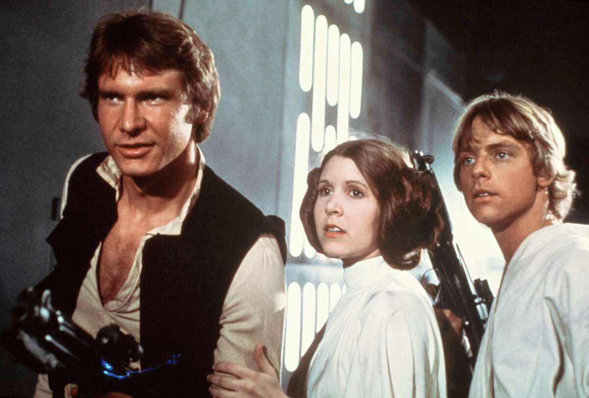 In this 1977 image provided by 20th Century-Fox Film Corporation, from left, Harrison Ford, Carrie Fisher, and Mark Hamill are shown in a scene from